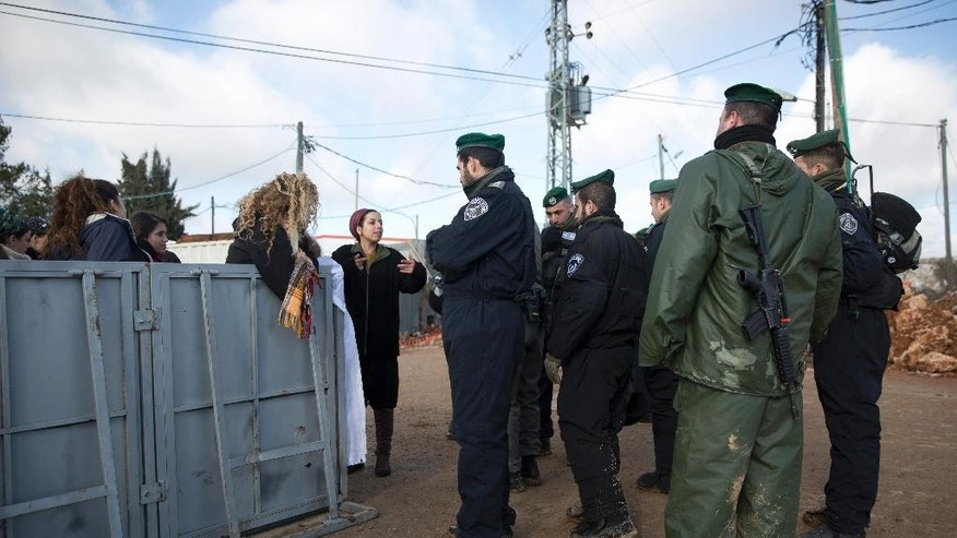 Settlers talk to Israeli police in Amona outpost,  Wednesday, Feb. 1, 2017. The military issued eviction orders the day before telling residents to evacuate Amona within 48 hours and blocked roads leading to the outpost. Thousands of soldiers and police gathered around Amona early Wednesday morning. (AP Photo/Oded Balilty)