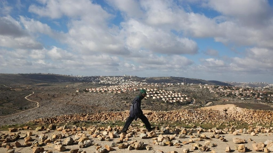 A settler walks outside Amona outpost,  Wednesday, Feb. 1, 2017. The military issued eviction orders the day before telling residents to evacuate Amona within 48 hours and blocked roads leading to the outpost. Thousands of soldiers and police gathered around Amona early Wednesday morning. (AP Photo/Oded Balilty)