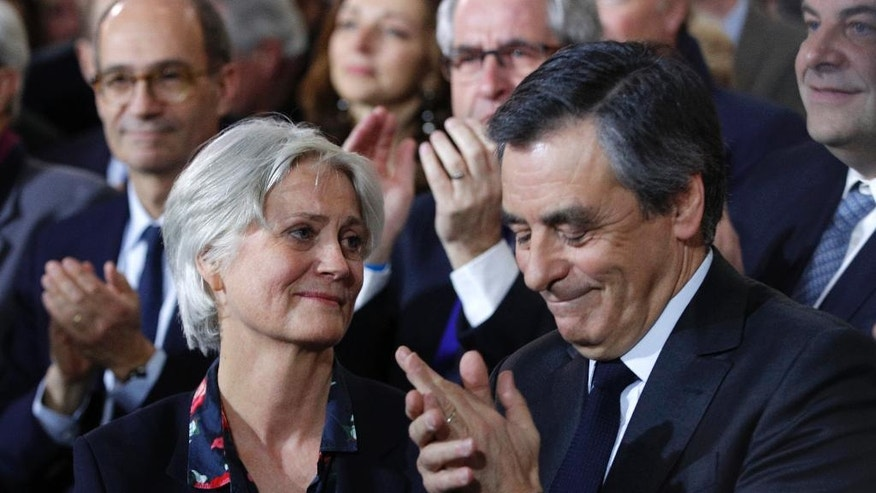 "FILE - In this Jan. 29, 2017 file photo, conservative French presidential candidate Francois Fillon applauds while his wife Penelope looks on as they attend a campaign meeting in Paris. Fillon is slowly finding his dream of winning the race under water. And it's because of the revelations of old-school satirical newspaper ""Le Canard Enchaine,"" or ""The Chained Duck."" The weekly's claims that Fillon's political clout helped secure handsomely paid jobs for his wife, Penelope, and two of their children are the just the latest scoops from the 102-year-old newspaper which is showing that traditional gumshoe reporting and the ink-and-paper format still have value in the increasingly online world. (AP Photo/Christophe Ena, File)"