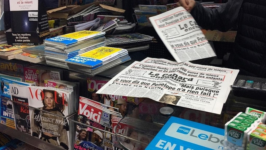"A newsstand owner picks up a copy of the satirical newspaper Canard Enchaine, or ""The Chained Duck"" in Paris, Wednesday, Feb. 1, 2017. The dirt-digging weekly's claims that conservative presidential candidate Francois Fillon's political clout helped secure handsomely paid jobs for his wife, Penelope, and two of their children are the just the latest scoops from the 102-year-old newspaper. (AP Photo/Bertrand Combaldieu)"
