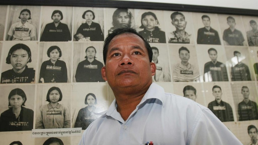 FILE -Jan. 25, 2007, file photo, Nhem En, former chief photographer at a torture center run by Cambodia's Khmer Rouge, poses for photo with dozens photographs of former prisoners in a room of Tuol Sleng genocide museum in Phnom Penh, Cambodia. The former Khmer Rouge photographer at the notorious S-21 prison has announced, Feb. 1, 2017, to form his own political party to participate the upcoming general election in 2018. (AP Photo/Heng Sinith, File)