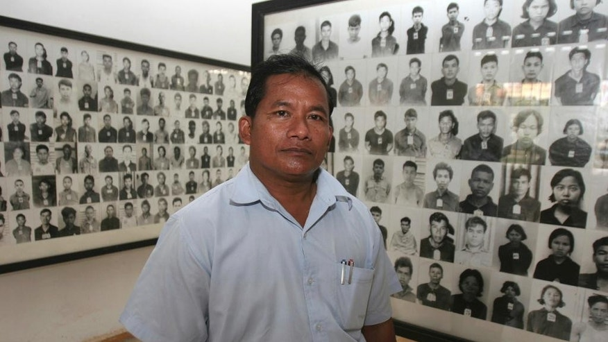 FILE -In this Jan. 25, 2007, file photo, Nhem En, former chief photographer at a torture center run by Cambodia's Khmer Rouge, poses for photo with dozens photographs of former prisoners in a room at the Tuol Sleng genocide museum in Phnom Penh, Cambodia. The former Khmer Rouge photographer at the notorious S-21 prison has announced, Feb. 1, 2017, to form his own political party to participate the upcoming general election in 2018. (AP Photo/Heng Sinith, file)