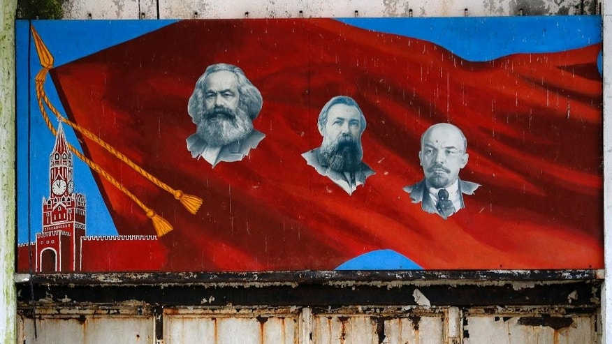 In this photo taken Friday, Nov. 7, 2014, a mural depicting Communist icons, from left, Karl Marx, Friedrich Engels and Vladimir Lenin hangs on a wall of a bomb assembly and repair facility in an abandoned ex-Soviet military base near Nagyvazsony, Hungary. For Hungary, a pro-Russian leader in the White House offers hope the Western world might end the sanctions imposed over Russia's annexation of Crimea and its role in eastern Ukraine. Many Poles, instead, fear a U.S-Russian rapprochement under Trump could threaten their own security interests. To most Poles, NATO represents the best guarantee for an enduring independent state in a difficult geographical neighborhood. (AP Photo/Darko Vojinovic)