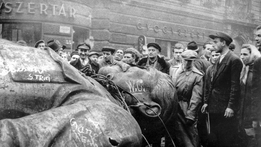 FILE - In this Oct. 24, 1956 file photo, people gather around a fallen statue of Soviet leader Josef Stalin in front of the National Theater in Budapest, Hungary. The uprising in Hungary began on Oct. 23, 1956 with demonstrations against the Stalinist regime in Budapest and was crushed eleven days later by Soviet tanks amid bitter fighting. For Hungary, a pro-Russian leader in the White House offers hope the Western world might end the sanctions imposed over Russia's annexation of Crimea and its role in eastern Ukraine. Many Poles, instead, fear a U.S-Russian rapprochement under Trump could threaten their own security interests. To most Poles, NATO represents the best guarantee for an enduring independent state in a difficult geographical neighborhood. (AP Photo/Arpad Hazafi, file)
