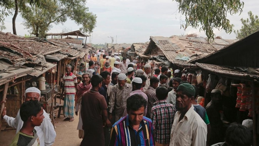 In this Dec. 2, 2016 file photo, Rohingya Muslims from Myanmar make their way in an alley at an unregistered refugee camp in Teknaf, near Cox's Bazar, a southern coastal district about, 296 kilometers (183 miles) south of Dhaka, Bangladesh. Rohingya Muslims in Bangladesh are worried about a government proposal to relocate them to a low-lying island deemed not ready for people to live there. Some 300,000 Rohingya Muslims have lived in Bangladesh for decades after fleeing there from neighboring Myanmar in the face of persecution by its military and majority Buddhists. An additional 66,000 Rohingya have arrived in Bangladesh since October, fleeing violent retaliation after the killings of nine Myanmar border police. (AP Photo/A.M. Ahad, File)