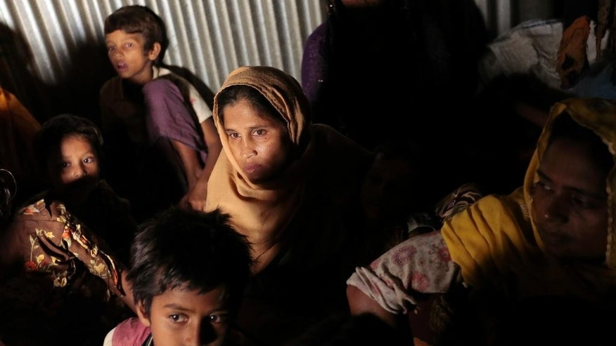 In this Dec. 2, 2016 file photo, Rohingya Muslims from Myanmar, who recently crossed over to Bangladesh, huddle in a room at an unregistered refugee camp in Teknaf, near Cox's Bazar, a southern coastal district about, 296 kilometers (183 miles) south of Dhaka, Bangladesh. Rohingya Muslims in Bangladesh are worried about a government proposal to relocate them to a low-lying island deemed not ready for people to live there. Some 300,000 Rohingya Muslims have lived in Bangladesh for decades after fleeing there from neighboring Myanmar in the face of persecution by its military and majority Buddhists. An additional 66,000 Rohingya have arrived in Bangladesh since October, fleeing violent retaliation after the killings of nine Myanmar border police. (AP Photo/A.M. Ahad, File)