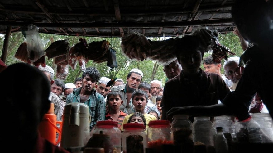 In this Dec. 2, 2016 file photo, Rohingya Muslims from Myanmar watch a television program about them being played on a mobile phone inside a tea stall, at an unregistered refugee camp in Teknaf, near Cox's Bazar, a southern coastal district about, 296 kilometers (183 miles) south of Dhaka, Bangladesh. Rohingya Muslims in Bangladesh are worried about a government proposal to relocate them to a low-lying island deemed not ready for people to live there. The proposal briefly posted on a government website in January, 2017, said a committee including representatives of the border guards and other agencies would prepare a list of hundreds of thousands of Rohingya Muslims to be relocated to the island of Thengar Char in southeastern Bangladesh. (AP Photo/A.M. Ahad, File)
