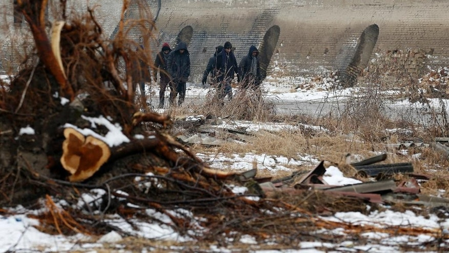 Migrants walk by an abandoned brick factory in the northern Serbian town of Subotica, near the border between Serbia and Hungary, Wednesday, Feb. 1, 2017. Thousands of migrants have been stranded in Serbia and looking for ways to cross illegally into the European Union. (AP Photo/Darko Vojinovic)