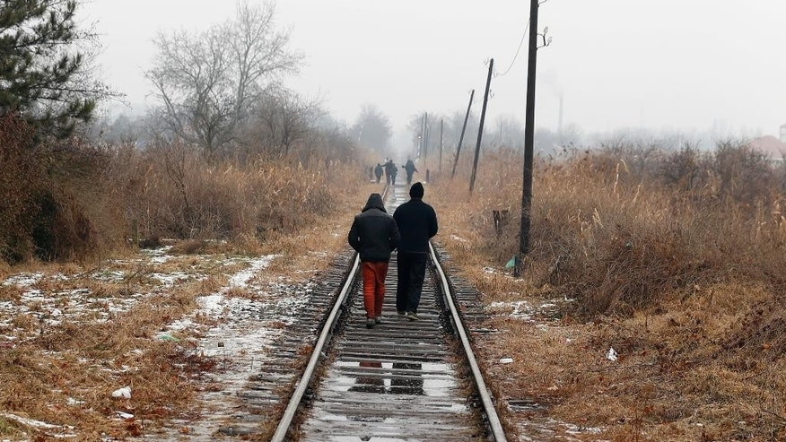 Migrants walk along train tracks close to the northern Serbian town of Subotica, near the border between Serbia and Hungary, Wednesday, Feb. 1, 2017. Thousands of migrants have been stranded in Serbia and looking for ways to cross illegally into the European Union. (AP Photo/Darko Vojinovic)