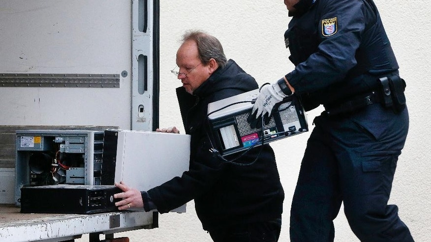 German police officers carry computers out of a mosque during a terror raid in Frankfurt, Germany, Wednesday, Feb. 1, 2017.(AP Photo/Michael Probst)