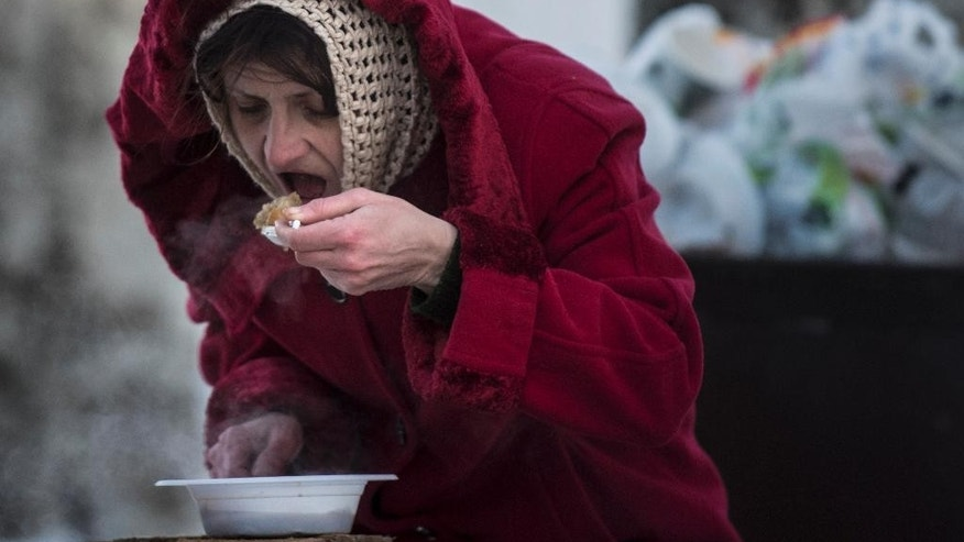 A local resident eats free food at a humanitarian aid center in Avdiivka, eastern Ukraine, Wednesday, Feb. 1, 2017. Freezing residents of an eastern Ukraine town battered by an upsurge in fighting between government troops and Russia-backed rebels flocked to a humanitarian aid center Wednesday to receive food and warm up. (AP Photo/Evgeniy Maloletka)