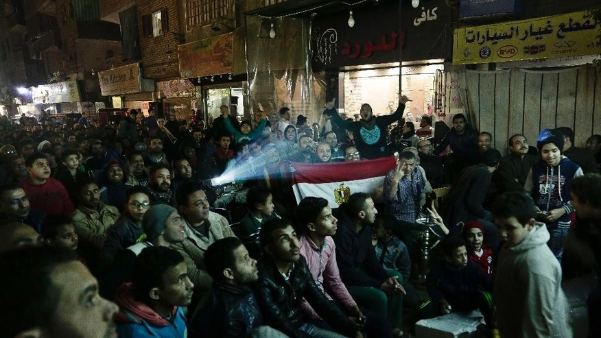 Egyptians watch the Egypt vs Burkina Faso semi-final match of the Africa Cup of Nations being held in Gabon on a large screen television in a street in the Imbaba neighborhood of Cairo, Egypt, Wednesday, Feb. 1, 2017. (AP Photo/Nariman El-Mofty)