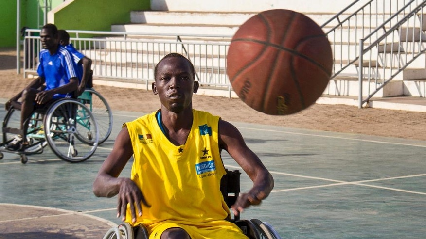 In this photo taken Friday, Jan. 20, 2017, a wheelchair basketball player receives the ball from a teammate, at a tournament following a two-week training session run by coach Jess Markt from Colorado, in Juba, South Sudan. Warnings of possible genocide hang over the world's youngest nation, but here on a basketball court under a fierce morning sun, South Sudan's civil war seems like another country. (AP Photo/Bullen Chol)