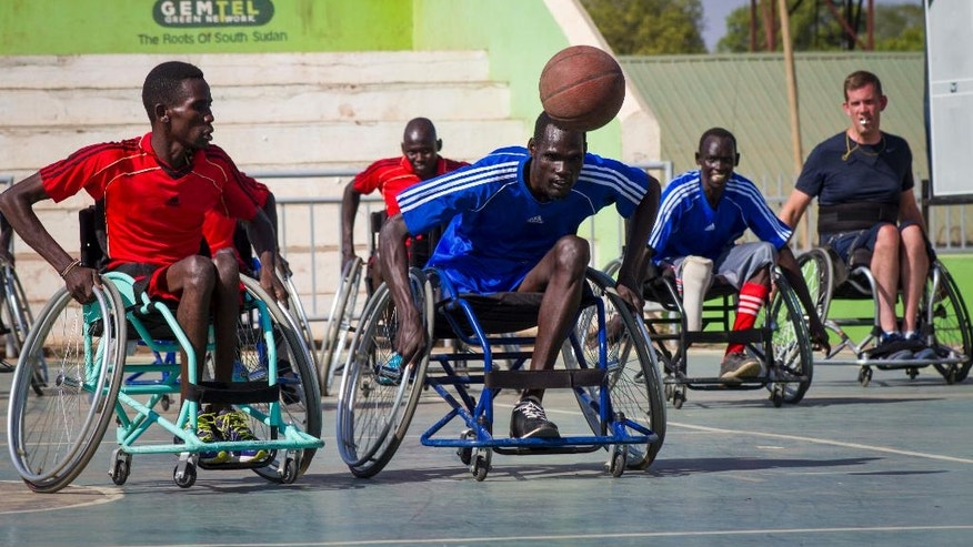 In this photo taken Friday, Jan. 20, 2017, wheelchair basketball players compete for the ball, at a tournament following a two-week training session run by coach Jess Markt from Colorado, far right, in Juba, South Sudan. Warnings of possible genocide hang over the world's youngest nation, but here on a basketball court under a fierce morning sun, South Sudan's civil war seems like another country. (AP Photo/Bullen Chol)