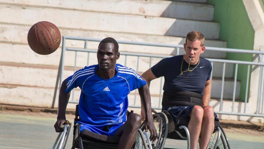 In this photo taken Friday, Jan. 20, 2017, a wheelchair basketball player eyes the ball as coach Jess Markt from Colorado, right, looks on, at a tournament following a two-week training session given by Markt in Juba, South Sudan. Warnings of possible genocide hang over the world's youngest nation, but here on a basketball court under a fierce morning sun, South Sudan's civil war seems like another country. (AP Photo/Bullen Chol)