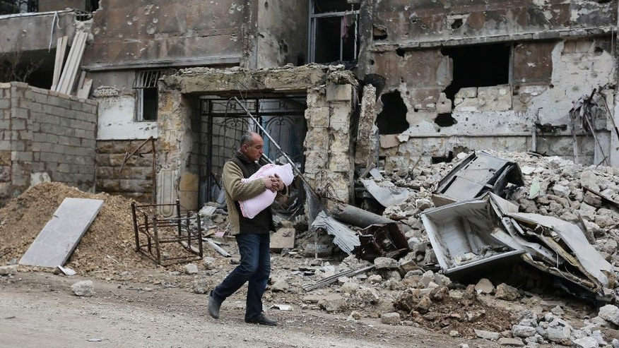 In this Jan. 20, 2017 photo, a Syrian man carries a baby as he walks past rubble in the once rebel-held Salaheddine neighborhood of eastern Aleppo, Syria. Aleppo, Syria's largest city, was widely brought to ruin by years of war, and now with Russia and Turkey leading peace efforts, international officials say it is time to start talking about rebuilding Aleppo and other cities. But there are few answers on how to do it, with the world reluctant to donate the billions needed and a political settlement in the war still uncertain and far off. (AP Photo/Hassan Ammar)