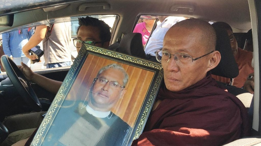 FILE - In this Monday, Jan. 30, 2017, file photo, a Buddhist monk holds a portrait of Ko Ni, legal adviser and prominent member of Myanmar's Muslim minority, during his funeral in Yangon, Myanmar. Myanmar police say a conspirator identified as Myint Swe behind the assassination of Ko Ni, a longtime legal adviser of the ruling party National League for Democracy and leader Aung San Suu Kyi, has been arrested and under interrogation since Monday. (AP Photo/Esther Htusan)