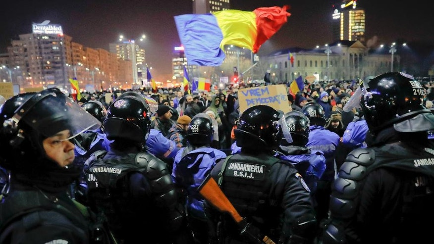 Romanian riot police protect the government building from crowds before minor clashes erupted during a protest in Bucharest, Romania, Wednesday, Feb. 1, 2017. Brief clashes broke out between protesters and police in Romania¹s capital, as tens of thousands of people protested for the second night a government decision to decriminalise official misconduct. (AP Photo/Vadim Ghirda)