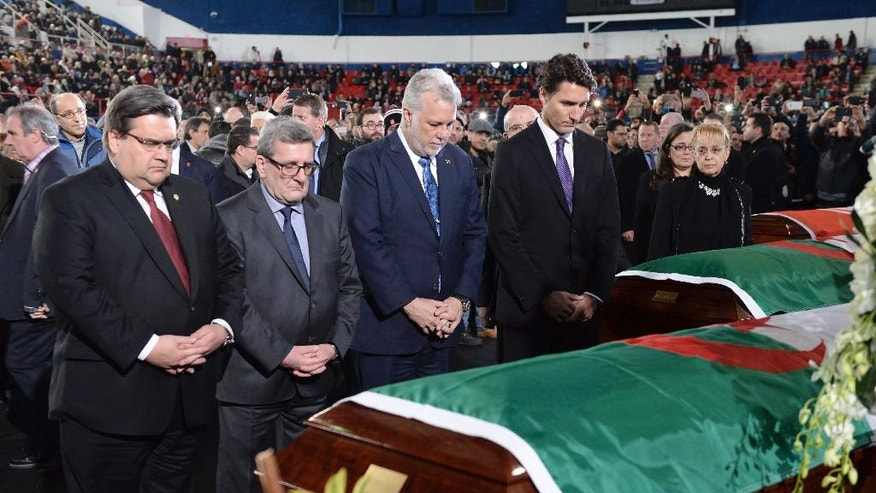 From right, Prime Minister Justin Trudeau,  Quebec Premier Philippe Couillard, Quebec City Mayor Regis Labeaume and Montreal Mayor Denis Coderre pay their respects to three of the six victims of the Quebec City mosque shooting, Abdelkrim Hassane, Khaled Belkacemi and Aboubaker Thabti,  during the funeral at the Maurice Richard Arena in Montreal, Thursday, Feb.  2, 2017.   (Paul Chiasson/The Canadian Press via AP)