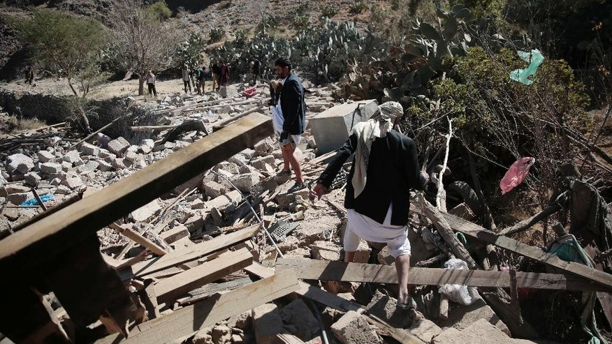 Men walk amid the rubble of a house destroyed by a Saudi-led airstrike on the outskirts of Sanaa, Yemen, Thursday, Feb. 2, 2017. (AP Photo/Hani Mohammed)