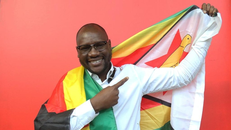 FILE - In this Tuesday May. 3, 2016 file photo, Evans Mawarire a young pastor in the Harare poses for a photo with the Zimbabwean flag wrapped around his body. A lawyer says a Zimbabwe pastor who fled to the United States after launching a popular protest movement has been arrested on his return home.  Lawyer Harrison Nkomo says Evan Mawarire was picked up at Harare International Airport on Wednesday, Feb. 1, 2017.  (AP Photo/Tsvangirayi Mukwazhi, File)