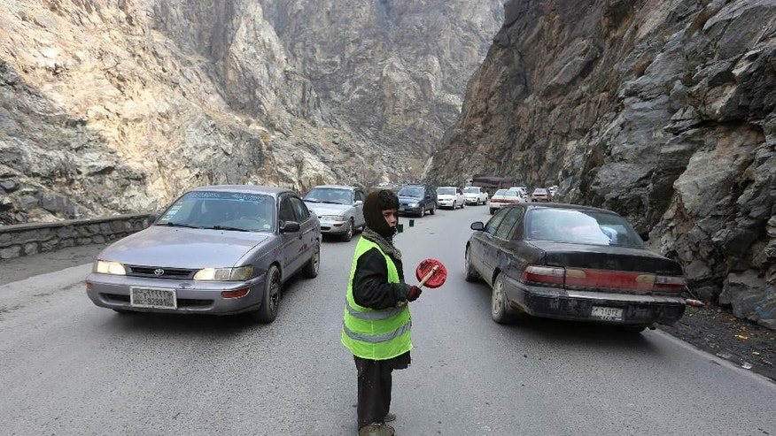 In this Jan. 5, 2017 photo, 11-year-old Sedaqat signals vehicles on the Maipur Pass, along the main highway from Kabul to Pakistan, near Kabul, Afghanistan. On the mountain pass outside Afghanistan's capital, trucks barreling down the highway slow down when 11-year-old Sedaqat waves his homemade sign to warn of a hairpin turn. He and other children spend the entire day out in the bitter cold, working as a volunteer traffic police on the most treacherous bends in the road and hoping to make up to $4 a day in tips. (AP Photo/Rahmat Gul)