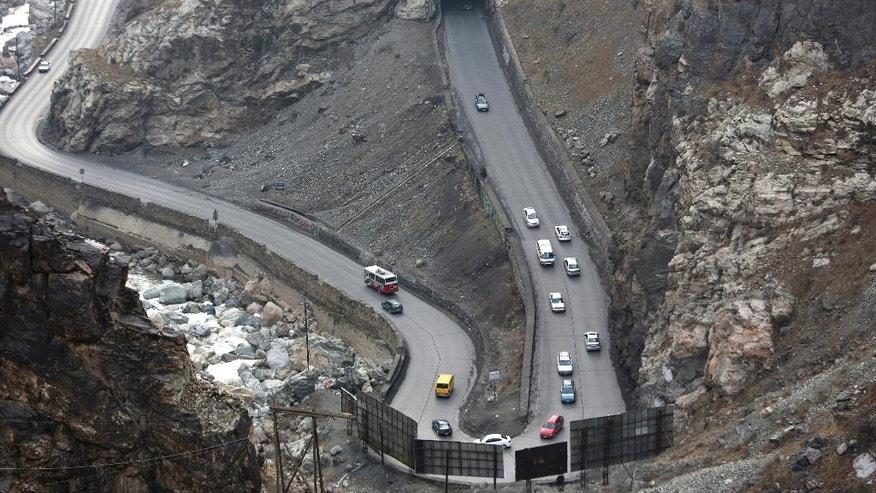 In this Jan. 5, 2017 photo, vehicles travel on the Maipur Pass, along the main highway from Kabul to Pakistan, near Kabul, Afghanistan. On the mountain pass outside Afghanistan's capital, trucks barreling down the highway slow down when 11-year-old Sedaqat waves his homemade sign to warn of a hairpin turn. He and other children spend the entire day out in the bitter cold, working as a volunteer traffic police on the most treacherous bends in the road and hoping to make up to $4 a day in tips. (AP Photo/Rahmat Gul)