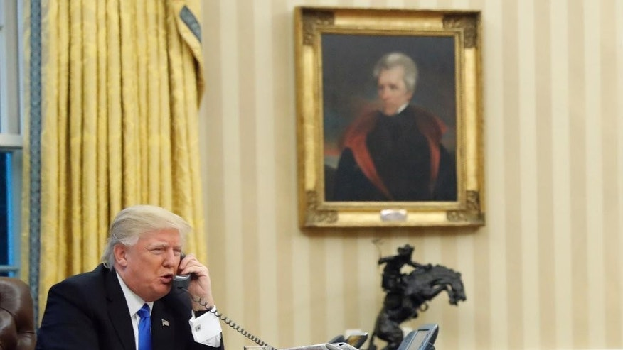 FILE - In the Jan. 28, 2017, file photo, U.S. President Donald Trump speaks on the phone with Prime Minister of Australia Malcolm Turnbull in the Oval Office of the White House in Washington. Amid the drama over a refugee resettlement deal between Australia and the United States, the White House has issued a series of conflicting statements on whether the agreement is still on, how many refugees it involves, and who, exactly, are the refugees. (AP Photo/Alex Brandon)