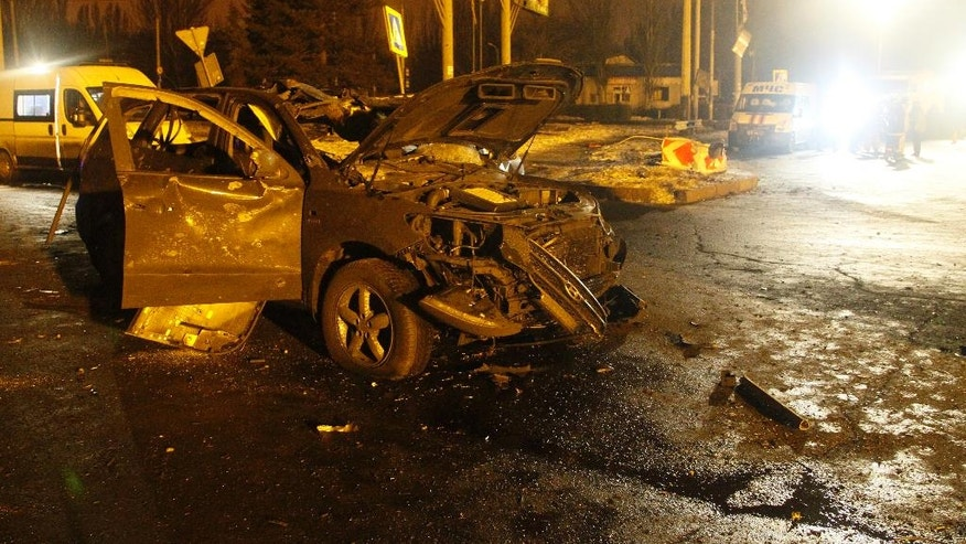 A car lies damaged on a street after artilley shook Donetsk, eastern Ukraine, late Thursday, Feb. 2, 2017. Salvos of artillery shook eastern Ukraine on Thursday, the fifth day of escalated fighting between government troops and Russia-backed separatist rebels. (AP Photo/Alexander Ermochenko)