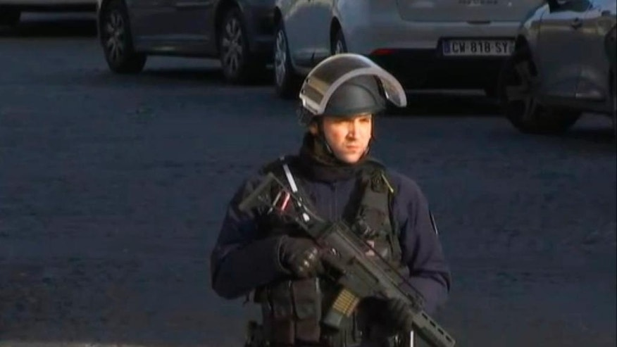 In this image made from video, a security official stands guard outside the Louvre Museum in Paris, France. Paris police said a soldier has opened fire outside the Louvre Museum. (AP Photo)