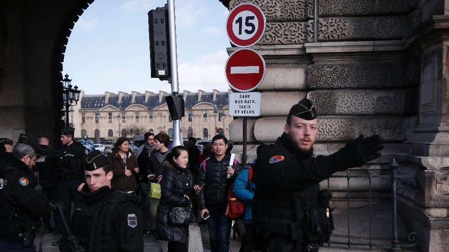 "Tourist leave the Louvre museum protected by police forces in Paris, Friday, Feb. 3, 2017. A French soldier shot and seriously wounded a man in a shopping mall beneath the Louvre Museum on Friday after he tried to attack them and shouted ""Allahu akbar,"" officials said. (AP Photo/Thibault Camus)"