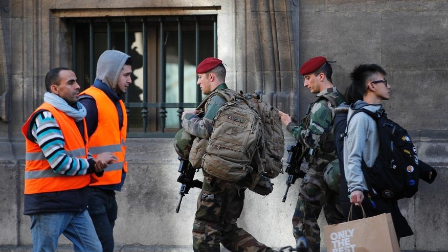 French soldiers patrol outside the Louvre museum near where a soldier opened fire after he was attacked in Paris, Friday, Feb. 3, 2017. Police say the soldier opened fire outside the Louvre Museum after he was attacked by someone, and the area is being evacuated. (AP Photo/Christophe Ena)