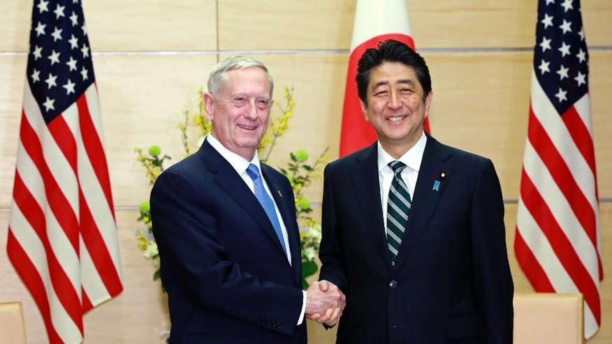 "U.S. Defense Secretary Jim Mattis, left, and Japanese Prime Minister Shinzo Abe, right, shake hands at the prime minister's office in Tokyo, Friday, Feb. 3, 2017.  In an explicit warning to North Korea, U.S. Defense Secretary Mattis on Friday said any use of nuclear weapons by the North on the United States or its allies would be met with what he called an ""effective and overwhelming"" response. (AP Photo/Eugene Hoshiko, Pool)"