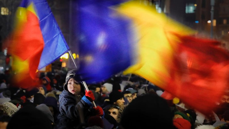 A child waves a Romanian flag during a protest joined by tens of thousands against a government decree that dilutes what qualifies as corruption, in Bucharest, Romania, Thursday, Feb. 2, 2017. Huge protests erupted in the capital and spread to cities around Romania in the past two nights after the government changed the law — one of the biggest protests in Romania since communism ended in 1989. (AP Photo/Vadim Ghirda)