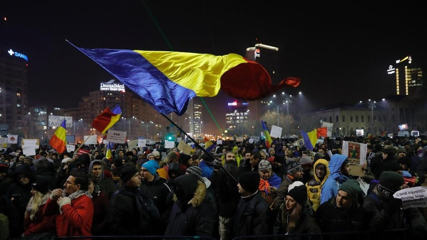 A protester waving a Romanian flag during a protest in Bucharest, Romania, Thursday, Feb. 2, 2017. Huge protests erupted in the capital and spread to cities around Romania in the past two nights after the government changed the law - one of the biggest protests in Romania since communism ended in 1989. (AP Photo/Vadim Ghirda)