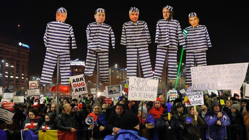 "Demonstrators carry puppets depicting, left to right, Justice Minister Floring Lordache, former Prime Minister Victor Ponta, head of the senate Calin Popescu Tariceanu, leader of the social democratic party Liviu Dragnea, and Prime Minister Sorin Grindeanu during a protest in Bucharest, Romania, Friday, Feb. 3, 2017. Romania's political crisis is deepening over a government decree that may benefit rich and powerful people convicted of corruption. Central banner reads: ""we came to steal because it is legal"". (AP Photo/Vadim Ghirda)"