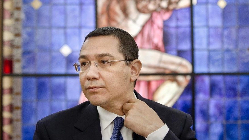 FILE - In this June 9, 2015 file photo, Romanian Prime Minister Victor Ponta adjusts his collar during a meeting with foreign media at the government headquarters in Bucharest, Romania. Victor Ponta was Romania's prime minister from 2012 until Nov. 2015 and former Social Democrat chairman, his government collapsed in the wake of street protests over a fire at a Bucharest nightclub where 64 died. (AP Photo/Vadim Ghirda)