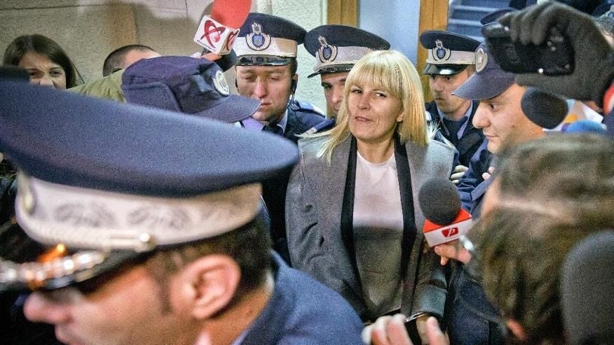 FILE - In this Tuesday, Feb. 10, 2015 file photo, Elena Udrea a 41-year-old Romanian politician who gained notoriety due to her close relationship with Traian Basescu, Romania's president from 2004 to 2014, is escorted by policemen as she exits the anti-corruption prosecutor's office in Bucharest, Romania. Elena Udrea is probably the most powerful woman politician of the last decade, although she failed to win a seat in Parliament in Dec. 2016 elections. (AP Photo/Vadim Ghirda, file)