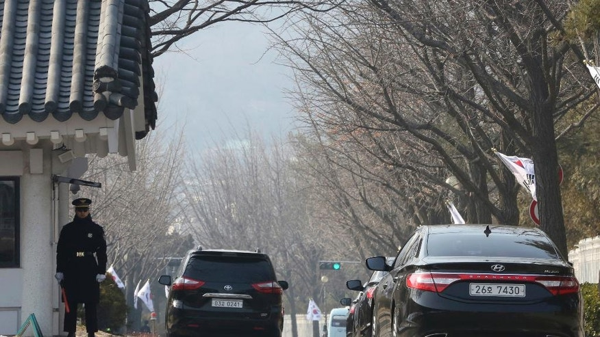Cars, right, from the independent counsel's office move toward the presidential Blue House in Seoul, South Korea, Friday, Feb. 3, 2017. South Korean officials Friday turned away prosecutors trying to search the president's mountainside compound, a confrontation that highlights the tensions of an investigation into a scandal that knocked President Park Geun-hye from power. (AP Photo/Ahn Young-joon)