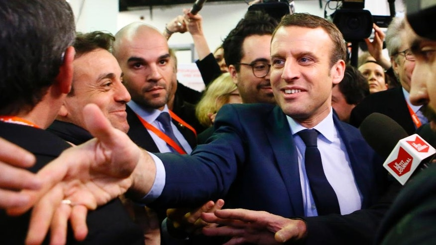 Presidential candidate Emmanuel Macron shakes hands at the Entrepreneurs Fair in Paris, Thursday, Feb. 2, 2017. With French President Francois Hollande having abandoned hopes of a second five-year term and conservative candidate Francois Fillon weakened, National Front leader Marine Le Pen and independent maverick candidate Macron are making hay. (AP Photo/Francois Mori)