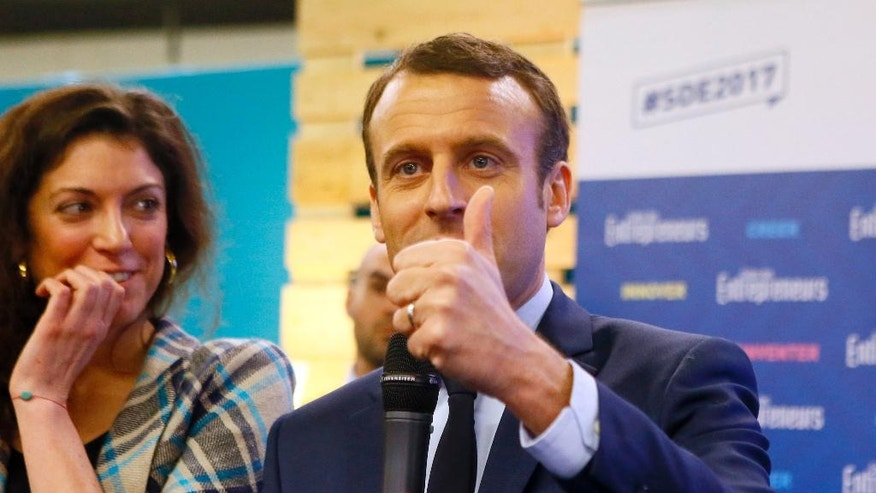 Presidential candidate Emmanuel Macron, right, speaks, as his top aide Axelle Tessandier, left, looks on, during a visit at the Entrepreneurs Fair in Paris, Thursday, Feb. 2, 2017. With French President Francois Hollande having abandoned hopes of a second five-year term and conservative candidate Francois Fillon weakened, National Front leader Marine Le Pen and independent maverick candidate Macron are making hay. (AP Photo/Francois Mori)