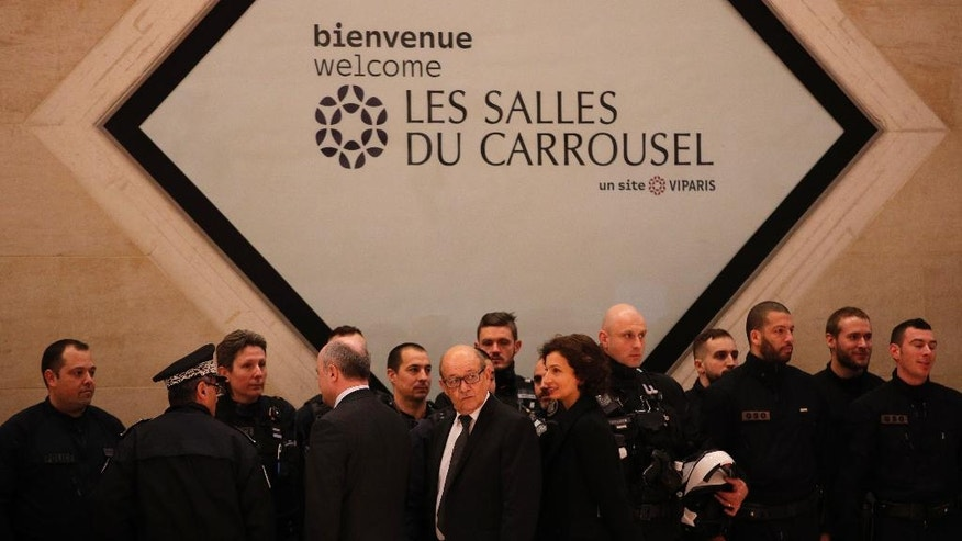 "French Interior Minisnter Bruno le Roux, center left, Defense Minister Jean-Yves le Drian, center, and Culture Minister Audrey Azoulay, center right, visit police forces inside the Louvre Museum after a shooting outside at the museum in Paris, Friday Feb. 3, 2017. A knife-wielding man shouting ""Allahu akbar"" attacked French soldiers on patrol near the Louvre Museum Friday in what the president called a terrorist attack. (AP Photo/Christophe Ena)"