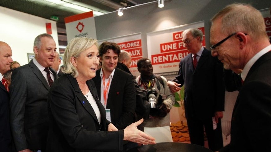Far-right leader and candidate for next spring presidential elections Marine le Pen, center left, shakes hands as she visits the Entrepreneur Fair, Wednesday, Feb. 1, 2017 in Paris, France. (AP Photo/Christophe Ena)