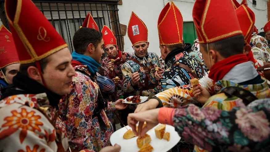 "In this Feb. 3, 2017 photo, members of the 'Endiablada' brotherhood eat on the street during the traditional festival in Almonacid del Marquesado, Spain. Since medieval times, the 400 residents of Almonacid del Marquesado have celebrated the ""Endiablada"" (Brotherhood of the Devils) festival each Feb. 2-3. Members of the town's all-male religious brotherhood dress up in what they consider devil-type characters, donning colorful jumpsuits and red miter hats. They each carry heavy copper cowbells around their waist, which they clang incessantly, and some run and jump to make as much noise as possible. Each man in the brotherhood also has his own wooden staff that they have inherited or carved, some of which include images of a devil. (AP Photo/Daniel Ochoa de Olza)"