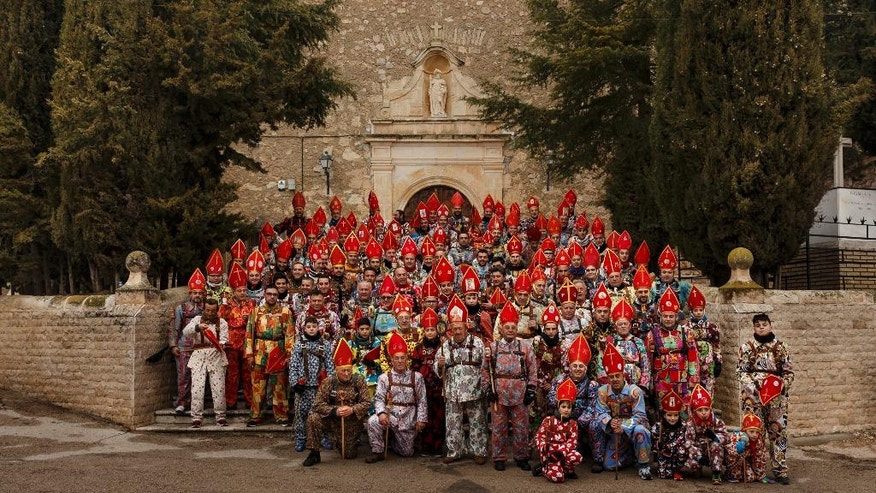 "In this Feb. 3, 2017 photo members of the Endiablada brotherhood pose for a group photo during the ""Endiablada"" traditional festival in Almonacid del Marquesado, Spain, Since medieval times, the 400 residents of Almonacid del Marquesado have celebrated the ""Endiablada"" (Brotherhood of the Devils) festival each Feb. 2-3. Members of the town's all-male religious brotherhood dress up in what they consider devil-type characters, donning colorful jumpsuits and red miter hats. They each carry heavy copper cowbells around their waist, which they clang incessantly, and some run and jump to make as much noise as possible. Each man in the brotherhood also has his own wooden staff that they have inherited or carved, some of which include images of a devil. (AP Photo/Daniel Ochoa de Olza)"