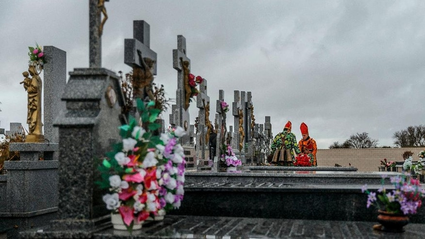 "In this Feb. 2, 2017 photo members of the Endiablada brotherhood pray for the deceased fellow believers and relatives in a cemetery during the ""Endiablada"" traditional festival in Almonacid del Marquesado, Spain. Since medieval times, the 400 residents of Almonacid del Marquesado have celebrated the ""Endiablada"" (Brotherhood of the Devils) festival each Feb. 2-3. Members of the town's all-male religious brotherhood dress up in what they consider devil-type characters, donning colorful jumpsuits and red miter hats. They each carry heavy copper cowbells around their waist, which they clang incessantly, and some run and jump to make as much noise as possible. Each man in the brotherhood also has his own wooden staff that they have inherited or carved, some of which include images of a devil. (AP Photo/Daniel Ochoa de Olza)"