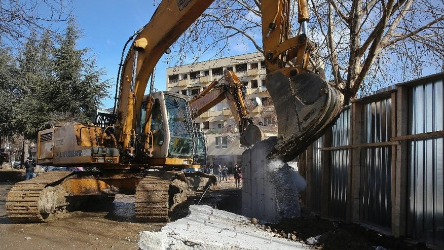 Bulldozers tear down a concrete wall erected in the northern city of Mitrovica on Sunday, Jan. 5, 2017, that has provoked tensions between Kosovo and neighboring Serbia. The wall removal followed an agreement between the government with the country's ethnic Serb minority, facilitated by the European Union and the United States embassy . (AP Photo/Visar Kryeziu)