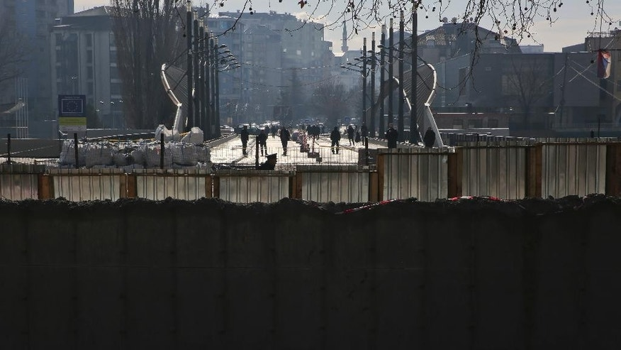 Ethnic Albanians walk in the bridge near a concrete wall erected in the northern city of Mitrovica on Sunday, Jan. 5, 2017, that has provoked tensions between Kosovo and neighboring Serbia as it was being pulled down. The move followed an agreement between the government with the country's ethnic Serb minority, facilitated by the European Union and the United States embassy . (AP Photo/Visar Kryeziu)