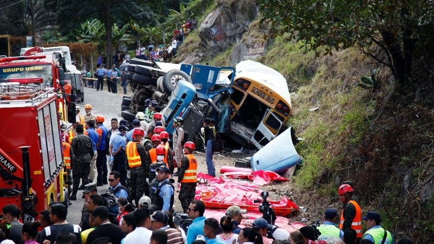 Emergency personnel respond to an accident involving a cargo truck and bus on the outskirts of Tegucigalpa, Honduras, Sunday, Feb. 5, 2017.  The cargo truck crashed into the bus on the highway outside Honduras' capital Sunday, killing more than a dozen people, authorities said. Police said the truck driver fled after the crash on a highway that links the capital with southern Honduras. (AP Photo/Fernando Antonio)