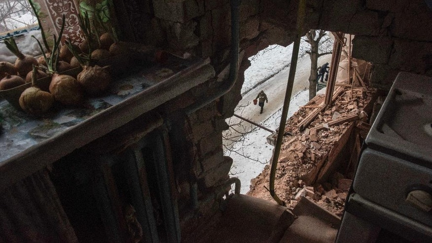 A local resident walking in a street is seen through a hole in an apartment building damaged by shelling in Avdiivka, Ukraine, Saturday, Feb. 4, 2017. Fighting in eastern Ukraine sharply escalated this week. The Ukrainian command said Saturday that several soldiers were killed in the past day. (AP Photo/Evgeniy Maloletka)